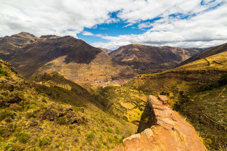 cusco region: Majestic landscape of the Sacred Valley from Pisac, Inca archeological site, major travel destination in Cusco region, Peru. Wide angle view from above with wall ruins in the foreground.