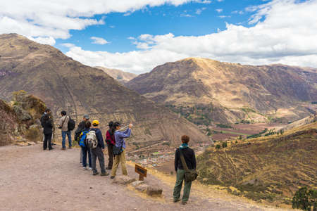 cusco region: Pisac, Peru - September 4, 2015: Group of tourists taking photos in the archeological site of Pisac, Sacred Valley, major travel destination in Cusco region, Peru. Vacations and adventures in South America.