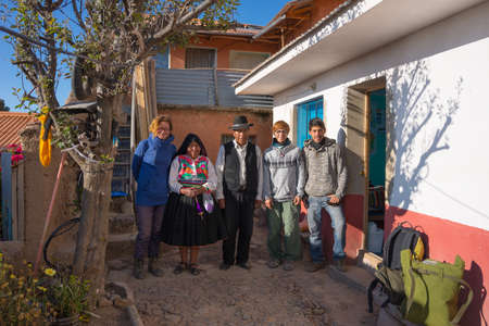 sustainable tourism: Amantani, Peru - September 1, 2015: Family in traditional clothings hosting tourists house on Amantani Island, Titicaca Lake, Peru. Concpet of sustainable and eco-friendly tourism.