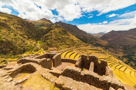 cusco region: Wide angle view of building and wall ruins with glowing majestic concentric terraces of Pisac, Incas site in Sacred Valley, major travel destination in Cusco region, Peru.