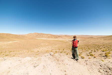 the one person: Barren mountain range and valley on the highlands of the Andes on the way to the famous Uyuni Salt Flat, among the most important travel destination in Bolivia. One person looking at camera in daylight. Stock Photo