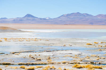 hot water geothermal: Hot water ponds in geothermal region of the Andean Highlands in Bolivia. Frozen salt lake, distant mountain range and barren volcanos in the background. Roadtrip to the famous Uyuni Salt Flat. Stock Photo
