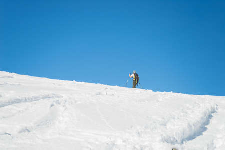 conquering: Back country skier hiking uphill on snowy slope by alpine ski touring. Concept of conquering adversities and reaching the target. Italian Alps, winter season, rear view.