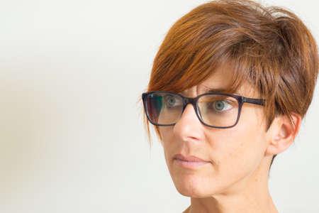 Taille portret van volwassen vrouw met rode haren, groene ogen, bril en ernstige gezichtsuitdrukking, tegen de muur staan. Natuurlijke zachte daglicht, natuurlijke huid, neutrale achtergrond.