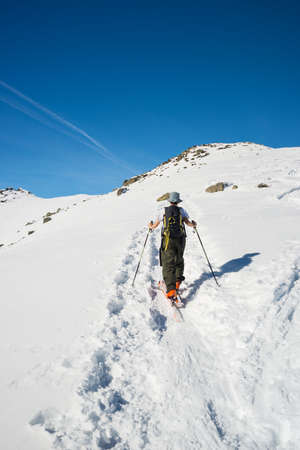 back country: Back country skier hiking uphill on snowy slope by alpine ski touring. Concept of conquering adversities and reaching the target. Italian Alps, winter season, rear view.