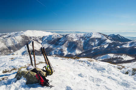back country: Double pair of back country ski and backpacks on the mountain summit. Stunning panoramic view of the alpine arc with clouds covering the valleys below. Concept of success and conquering the top.