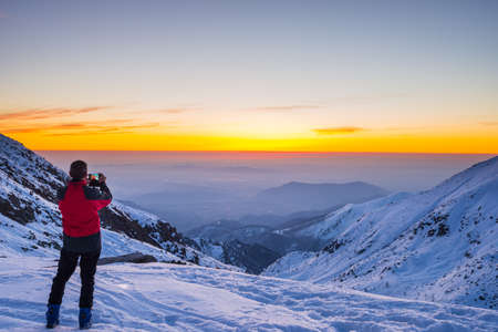 alpinist: Alpinist with phone in hand taking selfie on the mountain summit with majestic panoramic view of the Alps during dusk time. Concept of sharing life moments using new technology and wireless connection.