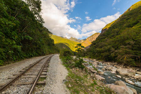 peru: The railroad track crossing jungle and Urubamba river, connecting Machu Picchu village to hydroelectric station, mostly used for tourism and cargo purpose. Machu Picchu archeological site visible towards the top in the background. Scenic sunset light on t Stock Photo