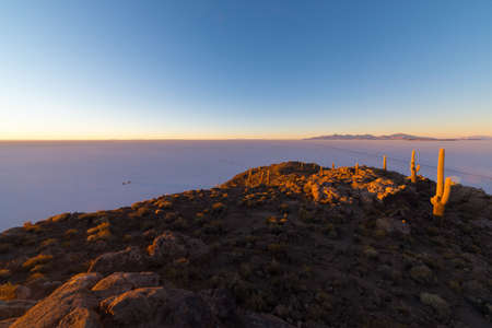 incahuasi: Colorful sunrise over the majestic Uyuni Salt Flat, among the most important travel destination in Bolivia. Wide angle shot from the summit of the Incahuasi Island with glowing rocks and cactus.