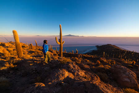 incahuasi: Tourist watching a warm sunrise over the majestic Uyuni Salt Flat, among the most important travel destination in Bolivia. Wide angle shot from the summit of the Incahuasi Island with glowing rocks and cactus. Stock Photo