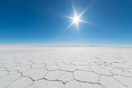Wide angle view of the world famous Uyuni Salt Flat, among the most important travel destination in the Bolivian Andes. Close up of hexagonal shapes of the salt pans in backlight.