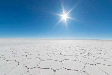 Groothoek oog van de wereldberoemde Uyuni Salt Flat, een van de belangrijkste reisbestemming in de Boliviaanse Andes. Close-up van de zeshoekige vorm van de zoutpannen in backlight.