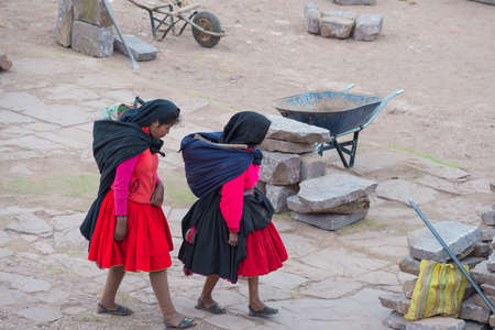 peruvian ethnicity: Taquile, Peru - September 1, 2015: Traditionally dressed women at work in Taquile Island, Titicaca Lake, Peru. About 2200 people live on the island. They speak Quechua language.