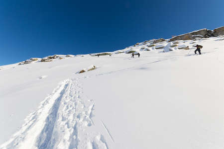 conquering: Alpinists hiking uphill by ski touring on snowy slope towards the mountain summit in a bright sunny day of spring. Concept of conquering adversities and reaching the goal. Italian Alps. Stock Photo