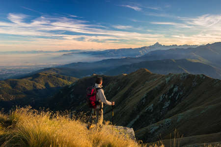 Hiker relaxing on the mountain summit at sunset and looking at majestic panorama of the italian Alps in autumn season. Wide angle view. Concept of conquering the success and healthy lifestyle.