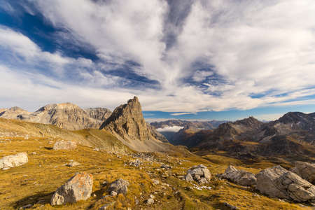 rocky mountain: Panoramic view of high mountain range in a colorful autumn with green yellow meadows and rocky mountain peaks. Wide angle shot in the Italian French Alps. Stock Photo