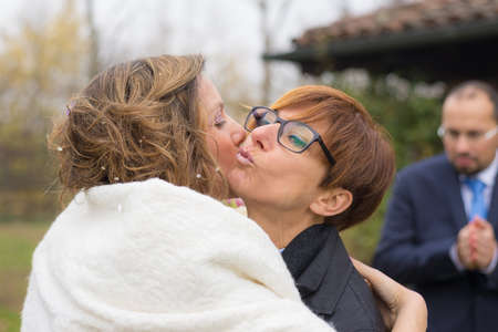 personas saludandose: Mejor amigo Felicitar, abrazar y besar a la novia durante la ceremonia de la boda. El novio de fuera de foco en el fondo. al aire libre tiro, gente real.