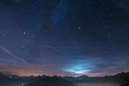 moonlight: The wonderful starry sky at Christmas time over the majestic high mountain range of the French Alps Italian. Glowing stars Altair and Vega with moonlight behind the clouds. Some two digital noise to high ISO. Stock Photo