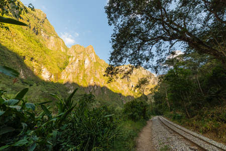 urubamba valley: The railroad track crossing jungle and Urubamba river, connecting Machu Picchu village to hydroelectric station, mostly used for tourism and cargo purpose. Machu Picchu archeological site visible towards the top in the background. Scenic sunset light on t Stock Photo