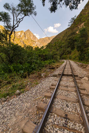 hydroelectric station: The railroad track crossing jungle and Urubamba river, connecting Machu Picchu village to hydroelectric station, mostly used for tourism and cargo purpose. Machu Picchu archeological site visible towards the top in the background. Scenic sunset light on t Stock Photo