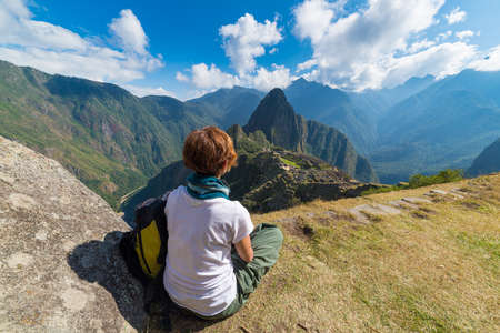 the one person: One person sitting in contemplation of Machu Picchu from the terrace above on daytime. The Incas city is the most visited travel destination in Peru. Stock Photo