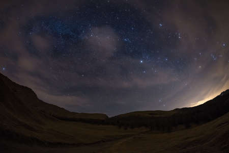 soul searching: The outstanding beauty of the starry sky and Milky Way in winter season, captured from black conifer woodland. Scenic distortion and 180° view due to fisheye lens, some acceptable digital noise due to 1600 iso setting. Stock Photo
