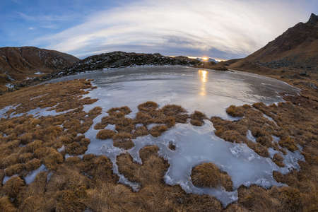 fisheye: High altitude alpine lake in idyllic land. Reflection of the sunlight on the frozen surface. Glowing sunstar at the horizon at sunset. Ultra wide angle fisheye on the Italian Alps at 2500 m asl.