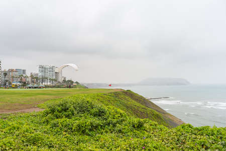 miraflores district: Paraglider launching from the coastline in Lima Miraflores, Peru. Winter season, cloudy and foggy sky, waving ocean. Skyline in the background. Unrecognizable people. Stock Photo