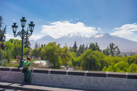guidebook: The majestic cone of El Misti Volcano in Arequipa, famous travel destination and landmark in Peru. Tourist reading travel guidebook. Concept of people traveling to scenic destination.