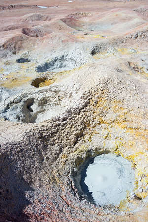 volcanos: Colorful hot water ponds in geothermal region of the Andean Highlands of Bolivia. Salt lake, mountain range and barren volcanos in the background. Roadtrip to the famous Uyuni Salt Flat. Stock Photo