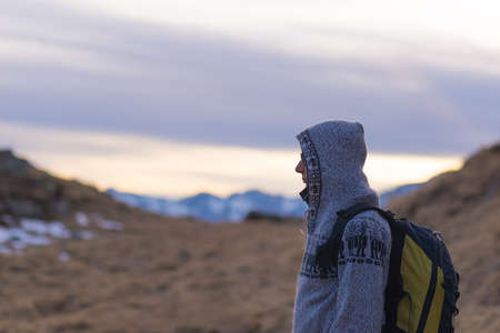 conquering adversity: Female hiker with backpack, jacket and hood resting in the cold on the italian Alps. Scenic sky at sunset, snowcapped mountain peak in the background. Selective focus, side view.
