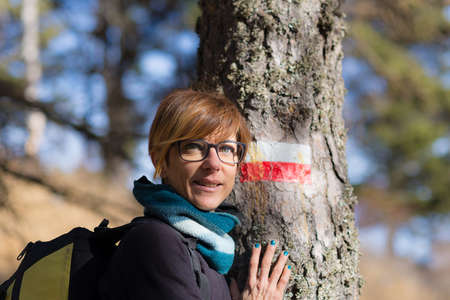 face in tree bark: Portrait of adult woman looking at the camera, with green eyes and cheerful facial expression, leaning on larch tree trunk with footpath sign on it. Natural daylight, natural skin, shot outdoors in alpine woodland.