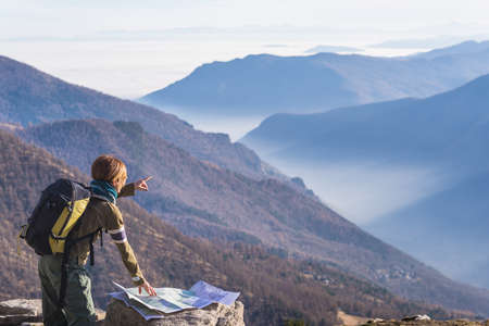 Female hiker with backpack reading trekking map while pointing finger to the mountains on the italian Alps. Mist and fog in the valley below, larch and pine tree forest around. Selective focus. 스톡 콘텐츠
