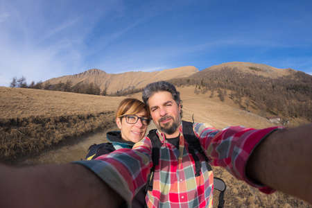 adventure travel: Adult couple taking selfie while hiking in the beautiful natural background of the italian Alps. Concept of freedom and adventures on the mountain. Cold tones, fisheye lens. Stock Photo