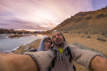 Adult couple taking selfie at sunset while hiking in the beautiful natural background of the italian Alps. Concept of freedom and adventures on the mountain. Wide angle fisheye lens.