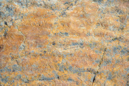 Sedimentary rock, multi colored claystone, with fractures and alteration pattern. Natural background, pattern and texture, yellow to dark red color. Stock Photo