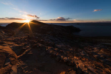 headland: Sunset in backlight on the Island of the Sun, Titicaca Lake, among the most scenic travel destination in Bolivia. Sunstar beyond the headland with glowing rocks in the foreground. Stock Photo
