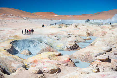 hot water geothermal: Huayllajc, Bolivia - August 25, 2015: Group of tourists looking at steaming hot water ponds and mud pots in geothermal region of Huayllajc on the Andean Highlands of Bolivia.