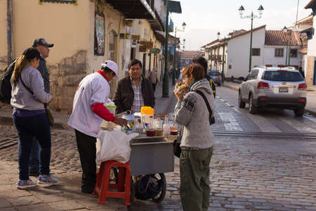 peruvian ethnicity: Cusco, Peru - September 3, 2015: People of peruvian ethnicity and tourists having breakfast in street of Cusco, former Inca capital, famous travel destination in Peru and one of the most visited historical cities in the world.