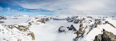 alpinist: Alpinist on mountain peaks and snowcapped ridges at high altitude in the italian french alpine arc. Scenic sky and clouds covering the valley below.
