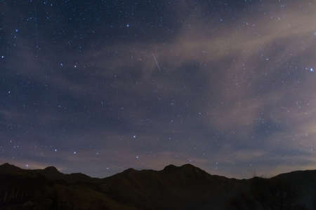 bardonecchia: The wonderful starry sky over the Italian Alps. Glowing Capella star at the right border. The Great Bear constellation (Ursa Major) and the Big Dipper on the bottom left. Some digital noise due to high iso.