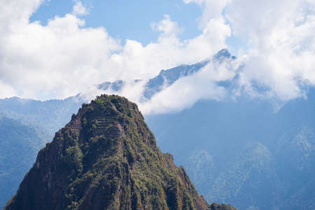 telephoto: People on Wayna Picchu mountain peak towering over Machu Picchu. The Incas city is the most visited travel destination in Peru. Telephoto view from distant. Stock Photo