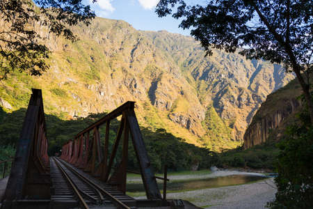 hydroelectric station: Iron bridge on the railroad track crossing jungle and Urubamba river, connecting Machu Picchu village to hydroelectric station, mostly used for tourism and cargo purpose. Scenic sunset light on the ridge. Stock Photo
