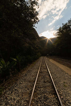 hydroelectric station: The railroad track crossing the jungle and connecting Machu Picchu village to hydroelectric station, mostly used for tourism and cargo purpose. Scenic sunset in backlight on the ridge. Stock Photo