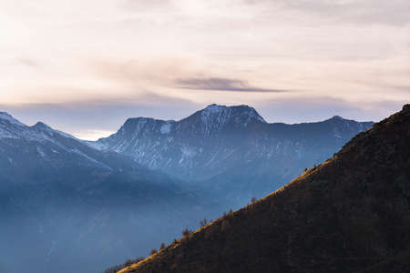 moody sky: Last sunlight hitting a steep ridge in the foreground with scenic cloudscape and moody sky over majestic snocapped mountain range in the background. Mist in the valley below, Italian French Alps. Stock Photo