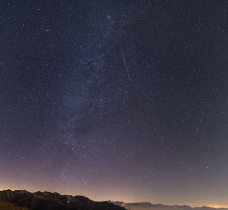 artificial satellite: The Milky Way and the starry sky from high up on the Alps with scenic mountain landscape. Andromeda galaxy on the upper left quadrant, an artificial satellite contrail in the center. Stock Photo