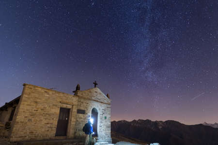 high up: The Milky Way and the starry sky from high up on the Alps with scenic mountain landscape. People standing aside a little chapel with lightning gear on. Stock Photo