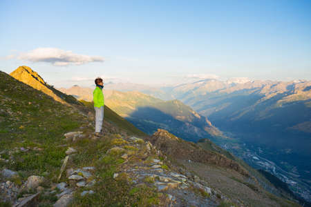 Woman watching stunning sunrise over valleys, ridges and mountain peaks. Wide angle view from 3000 m in Valle d'Aosta. Summer adventures on the italian Alps.