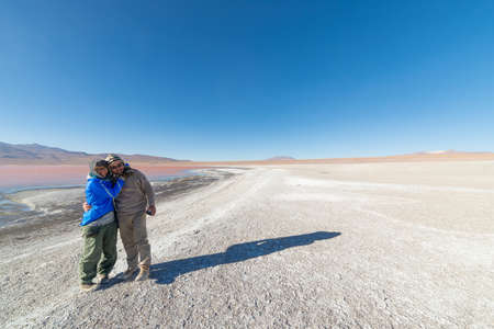 expansive: Couple hugging at Laguna Colorada with expansive view on barren mountain range and high altitude desert on the highlands of the Andes on the way to the famous Uyuni Salt Flat, Bolivia.