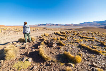 expansive: Tourist walking on the desert highlands of the Andes. Roadtrip to the famous Uyuni Salt Flat, among the most important travel destination in Bolivia. Expansive landscape of barren mountain range and salt lakes.